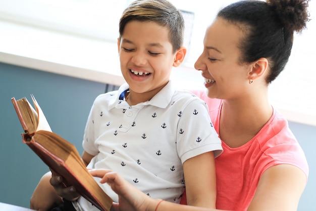 Mãe lendo um livro para seu filho pequeno Foto gratuita