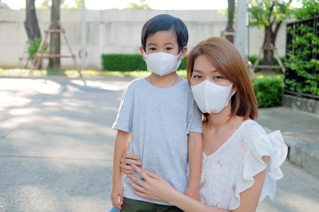 Mãe nova asiática que veste a máscara protetora pm2.5 para seu filho em exterior Foto Premium