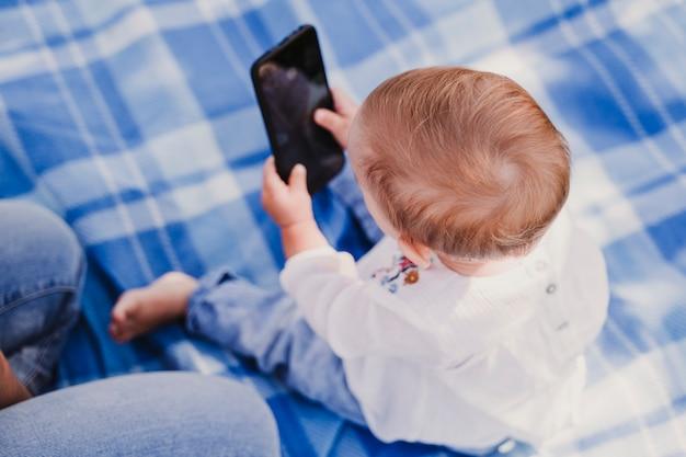 Mãe nova e bebê feliz que usam o telefone móvel ao ar livre. conceito de tecnologia Foto Premium