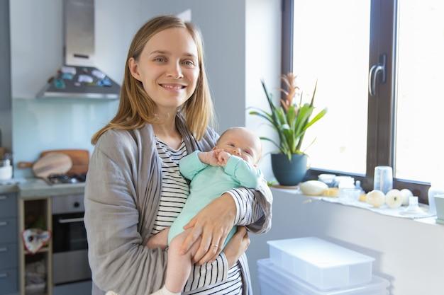 Mãe nova positiva que balança o bebê alegre Foto gratuita