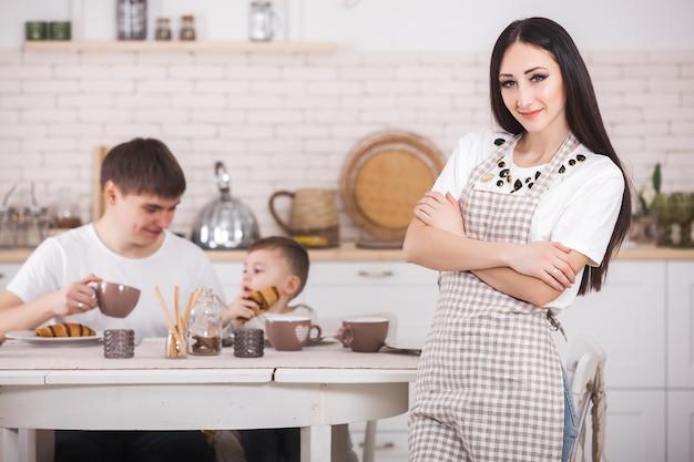 Mãe nova que está na frente de sua família na cozinha. família feliz jantando ou café da manhã. mulher fazendo o jantar para o marido e o bebê. Foto Premium