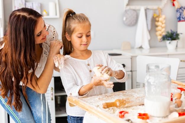 Mãe olhando para a filha cozinhar Foto gratuita