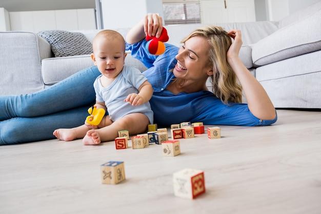 Mãe olhando para bebé que joga com os brinquedos na sala de estar Foto gratuita