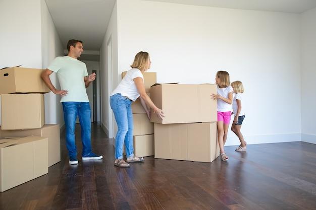 Mãe, pai, duas meninas carregando caixas e empilhando em seu novo apartamento vazio Foto gratuita