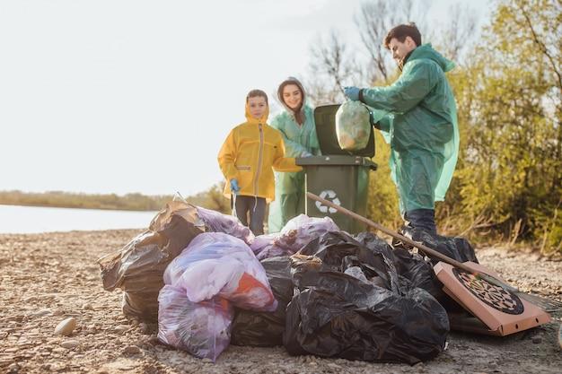 Mãe, pai e dson com um grupo de voluntários, recolhendo lixo na praia. Foto Premium
