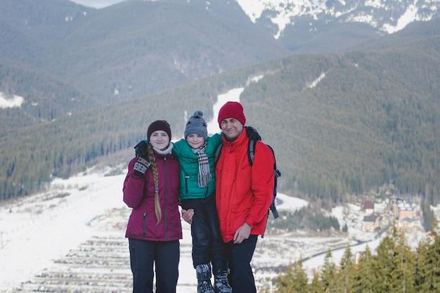 Mãe, pai e filho estão de pé e sorrindo Foto Premium