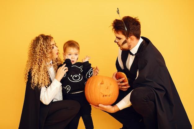 Mãe, pai e filhos em fantasias e maquiagem. pessoas de pé sobre um fundo amarelo. Foto gratuita