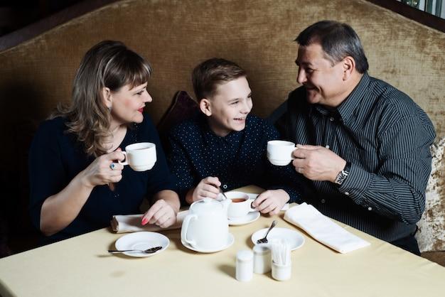 Mãe, pai, filho bebem chá Foto Premium