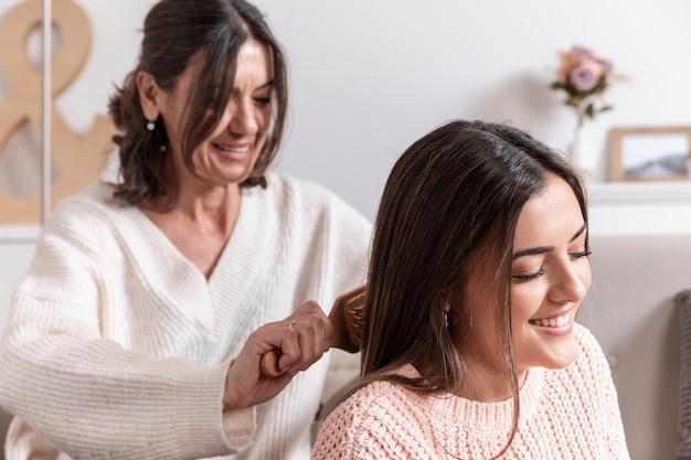 Mãe, penteando o cabelo da filha Foto gratuita
