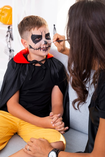 Mãe pintando o rosto de seus filhos para o halloween Foto gratuita