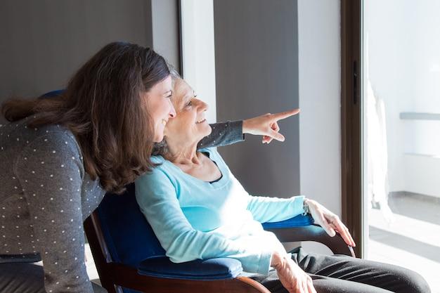 Mãe positiva e filha que apreciam a vista dramática Foto gratuita