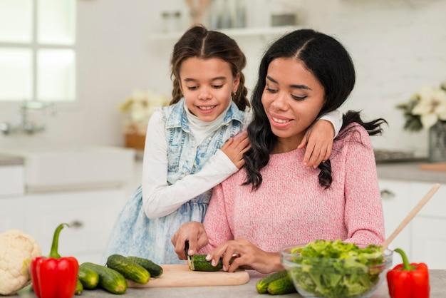 Mãe preparando comida para a filha Foto gratuita