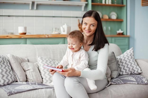 Mãe se senta em um sofá com uma criança, lê um livro e olha fotos brilhantes Foto Premium