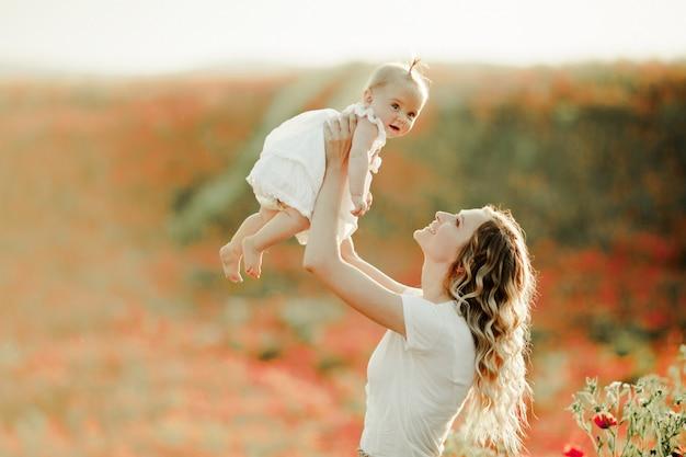 Mãe segura seu bebê em altura no campo de papoulas Foto gratuita