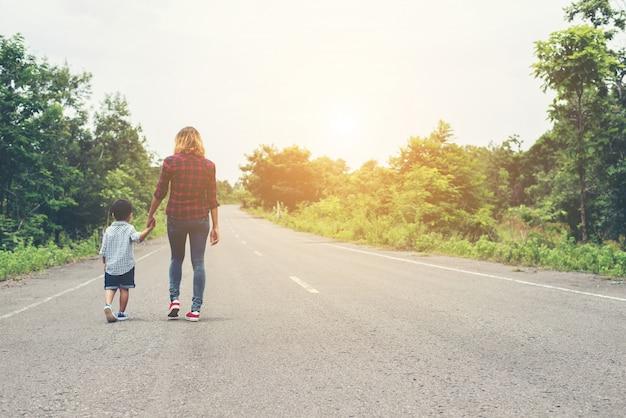 Mãe segurando a mão de seu filho no dia de verão andando na rua Foto gratuita