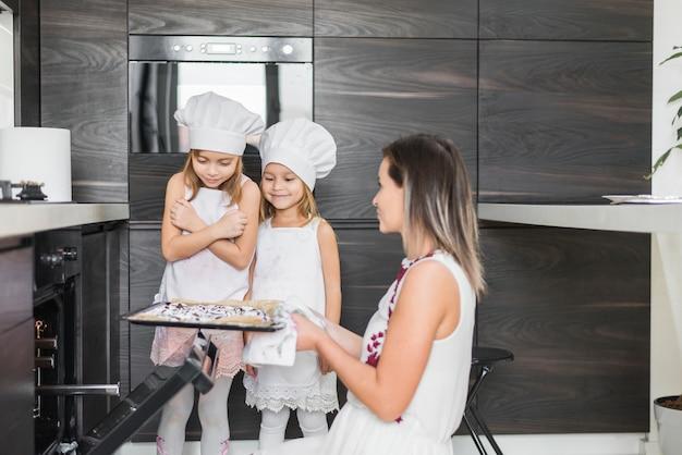 Mãe, segurando, bolinhos cozidos, em, bandeja, enquanto, olhar, dela, filhas Foto gratuita