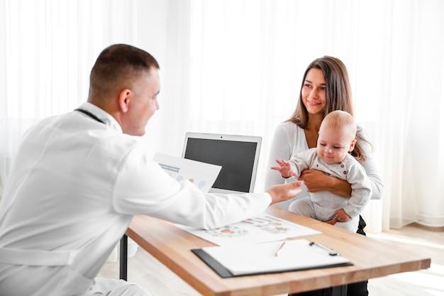 Mãe, segurando o bebê e olhando para o médico Foto gratuita