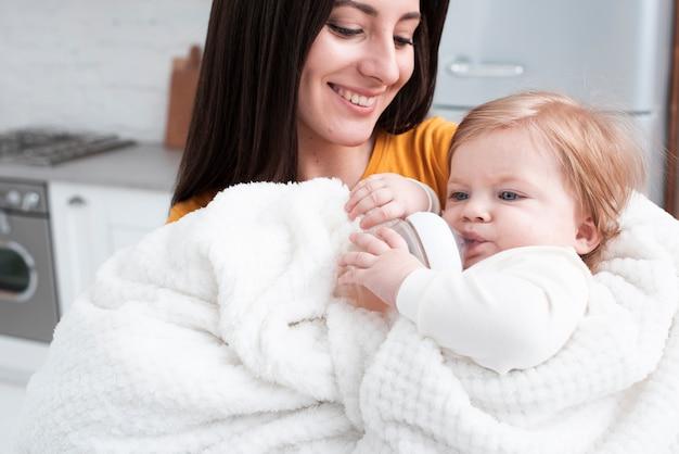 Mãe, segurando o bebê no cobertor fofo Foto gratuita