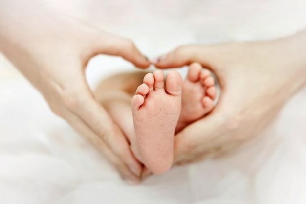 Mãe, segurando os pés de mãos do bebê recém-nascido. formato de coração. ame. Foto Premium