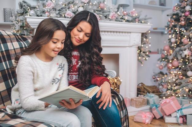 Mãe sentado junto com a filha e olhar para o livro. eles leram. menina segura com as duas mãos. eles estão em um quarto decorado. há árvore de natal e lareira atrás deles. Foto Premium
