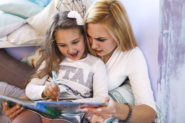 Mãe séria e filha sorriu estão escrevendo no caderno na sala iluminada Foto gratuita