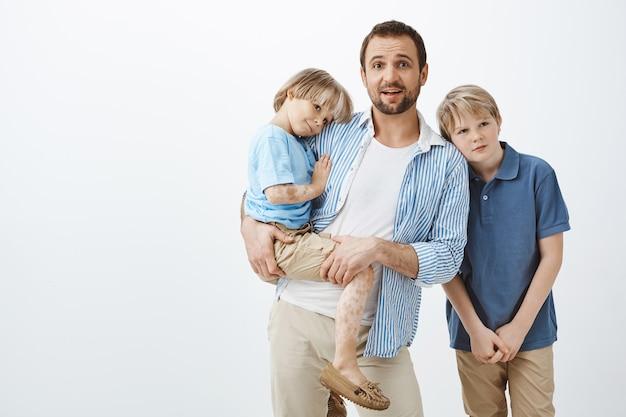 Mãe solteira cuidando de filhos. pai segurando uma criança bonita com vitiligo enquanto olha nervoso, sendo deixado sozinho com dois meninos, sem noção de como cuidar de crianças Foto gratuita