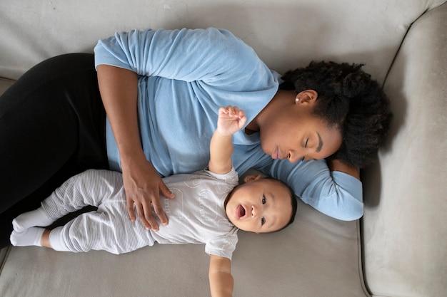 Mãe solteira deitada em um sofá com seu filho bebê durante o bloqueio covid19 Foto gratuita