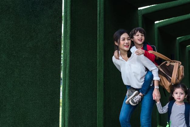 Mãe solteira que leva e que joga com suas crianças no jardim com fundo verde da parede. Foto Premium