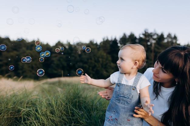 Mãe tem filhinha nos braços enquanto balões de sabão voam em volta deles Foto gratuita