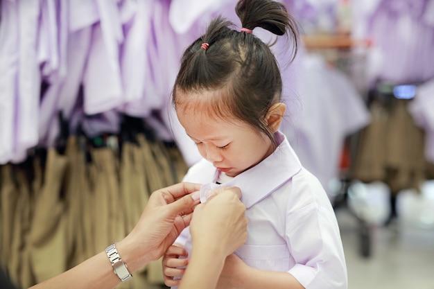 Mãe tenta vestir uniforme escolar para sua filha, crianças do jardim de infância. Foto Premium