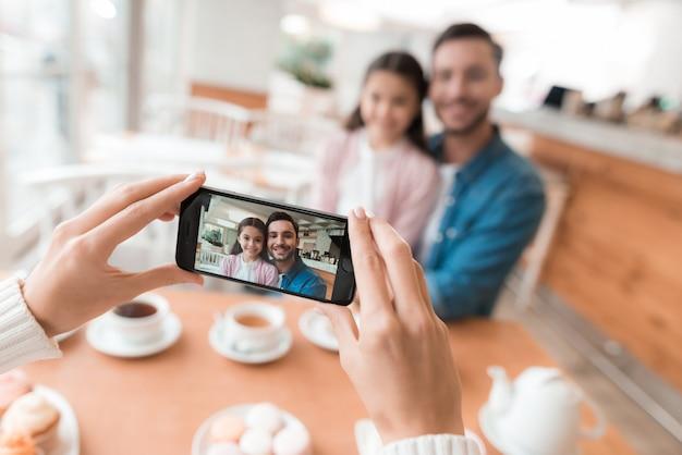 Mãe tira fotos de sua família no smartphone. Foto Premium