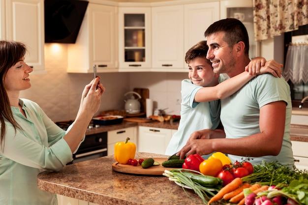 Mãe tirando uma foto de pai e filho na cozinha Foto gratuita