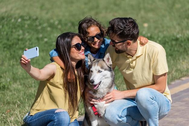 Mãe tirando uma selfie de família com cachorro no parque Foto gratuita