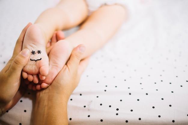 Mãe tocando os pés do bebê com o smiley Foto gratuita