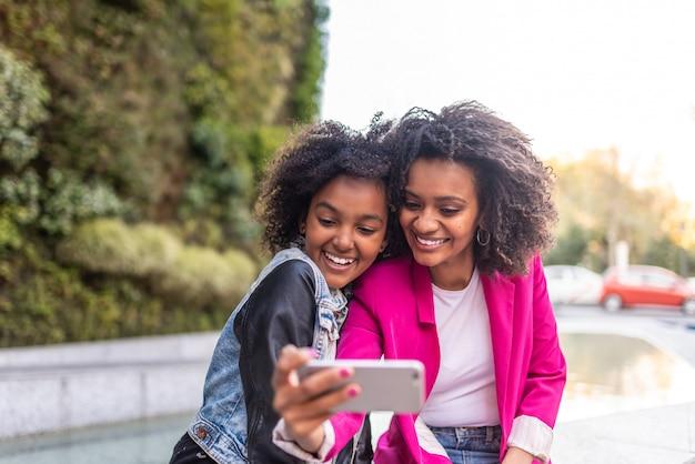 Mãe tomando um selfie com a filha. Foto Premium
