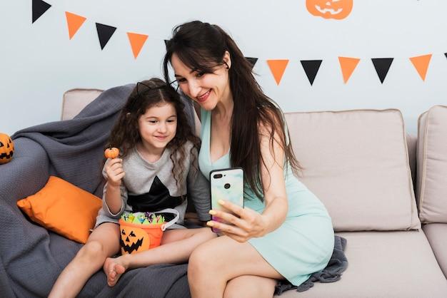 Mãe tomando uma selfie com a filha no dia das bruxas Foto gratuita
