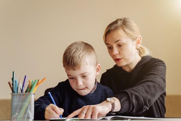 Mãe usando laptop e tablet ensinando com o filho on-line em casa no quarto dele Foto gratuita