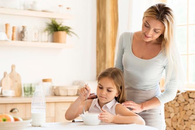 Mãe vendo sua filha tomar café da manhã Foto gratuita
