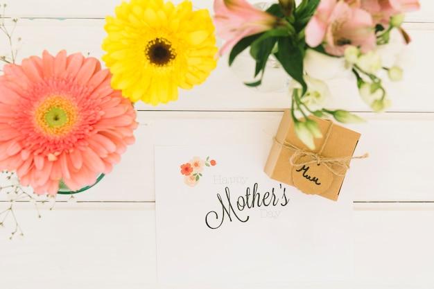 Mães inscrição com gerbera e caixa de presente Foto gratuita
