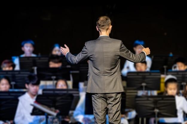 Maestro da banda masculina conduzindo sua banda de concerto Foto Premium