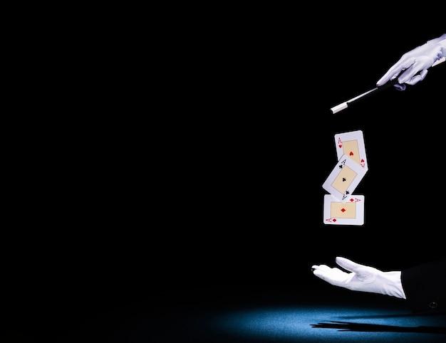 Mágico, executando o truque de cartão de jogo com a varinha mágica contra o fundo preto Foto gratuita