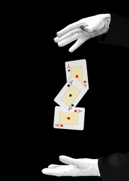 Mágico, executando o truque do cartão de jogo contra o fundo preto Foto gratuita
