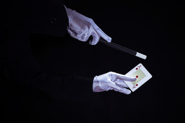 Mágico que executa o truque no cartão de jogo dos áss contra o fundo preto Foto gratuita