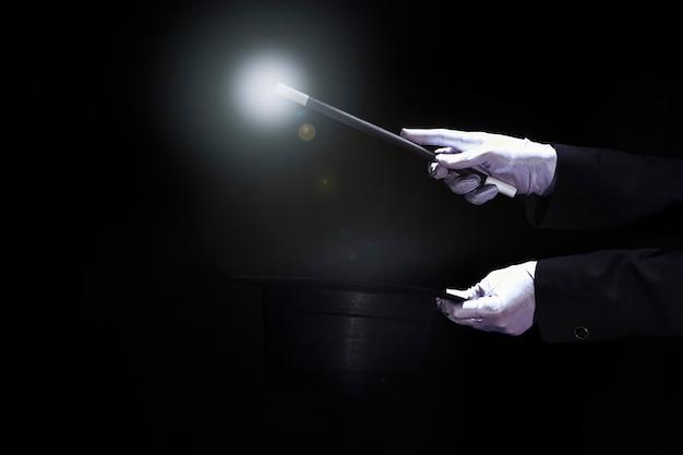 Mágico realizando truque com varinha mágica sobre a cartola preta contra fundo preto Foto gratuita