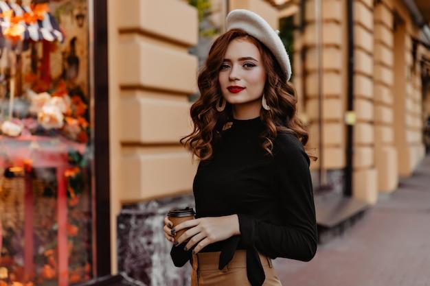 Magnífica garota europeia na boina marrom, passando o tempo ao ar livre. curiosa senhora francesa de gengibre em pé na rua e bebendo chá. Foto gratuita
