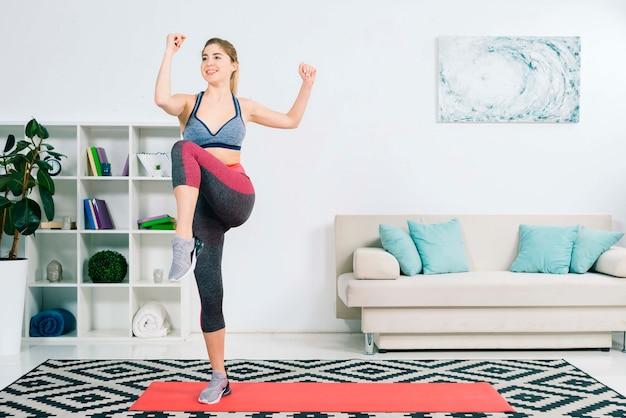 Magro feminino em activewear fazendo exercício na sala de estar Foto gratuita