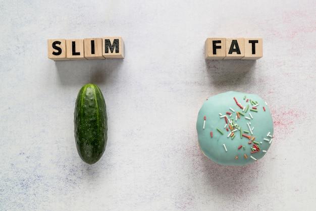 Magro; texto gordo em blocos de madeira com pepino e donut vitrificada sobre pano de fundo áspero Foto gratuita