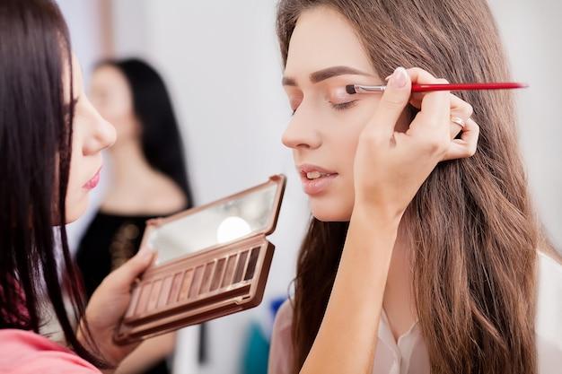 Make-up artist faz maquiagem para uma linda garota em um salão de beleza Foto Premium