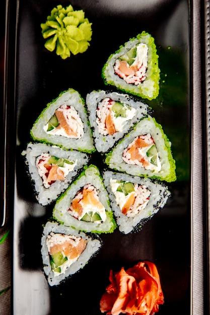 Maki com creme de salmão e caranguejo. queijo arroz pepino gengibre wasabi vista superior Foto gratuita