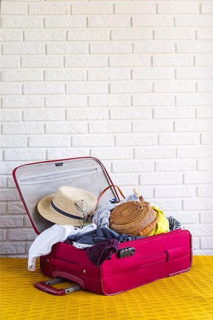 Mala cheia de roupas femininas para as férias de verão Foto Premium